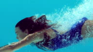 Brunette woman swimming underwater video