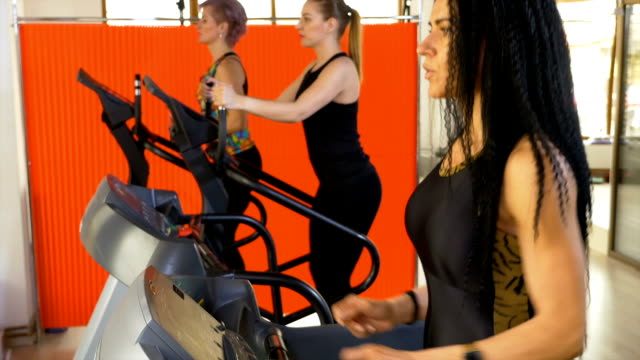 Brunette woman using activity fitness tracker app on smartwatch while jogging on treadmill video