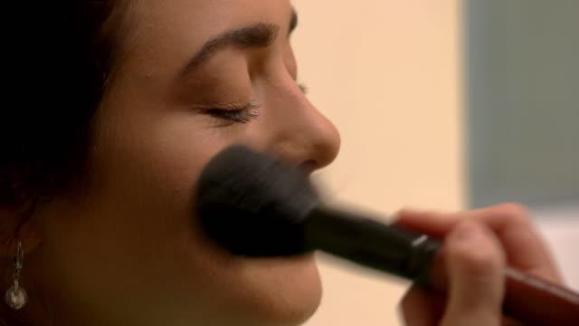 Brush applying makeup on woman. video