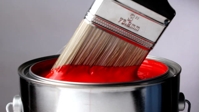Brush in can of red paint video