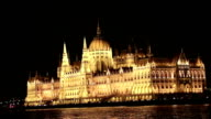Budapest Parliament at Night. Evening capture of Hungary's parliament building, illuminated, with a cruise ship sailing past on the River Danube video