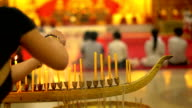 Buddha day in buddhist temple. People set candles, flowers and incense sticks. Wat Nakha Ram, Phuket, Thailand. FullHD video