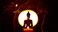 Buddha statue and candle with hand holding incense video
