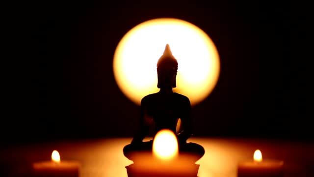 Buddha statue and moving candle flames video