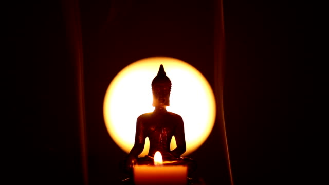 Buddha statue with candle and incense smoke video
