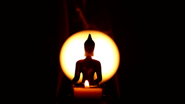 Buddha statue with candle and lateral incense smoke video
