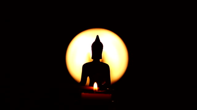 Buddha statue with candle and moving incense stick video