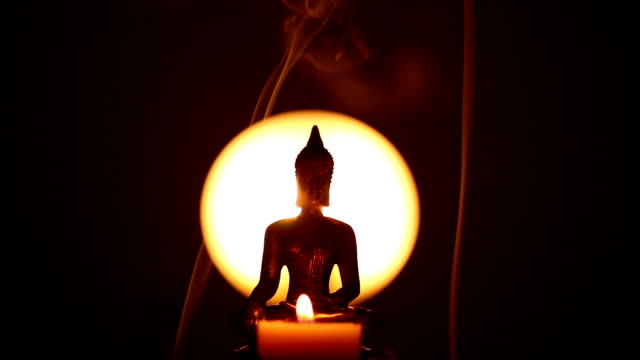 Buddha statue with one candle and incense smoke video