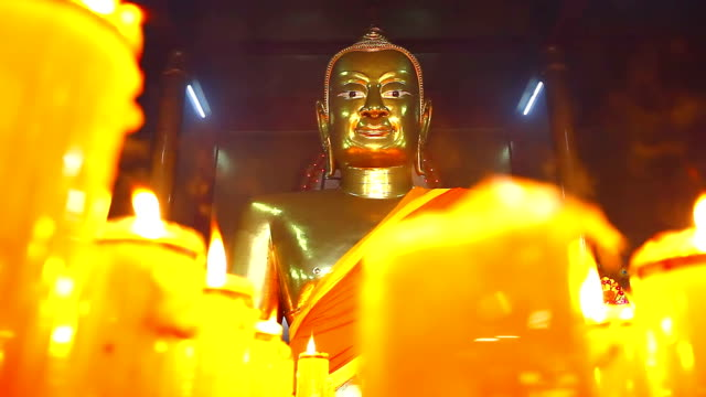 Buddha statuettes with candles in temple video