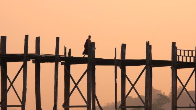 Buddhist Monk Walking Over U Bein Bridge at Sunrise, Mandalay, Myanmar (Burma) video