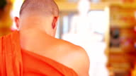 Buddhist monk with orange robe pray in temple video