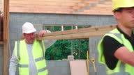 Builder And Apprentice Carrying Wood On Construction Site video