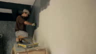 Builder carefully paints wall in gray colour using special roller video