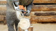 Builder handles wooden timber chainsaw. Against the background is part of the future of the house made of wooden beams, slow motion video