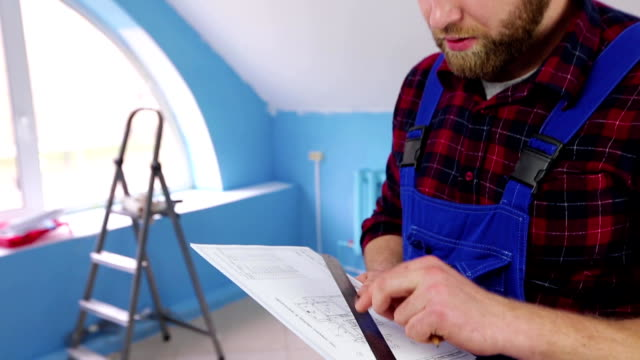 Builder looking at a plan of the repair video