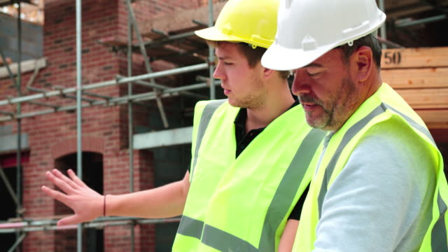 Builder On Building Site Discussing Work With Apprentice video