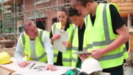 Builder On Building Site Discussing Work With Apprentices video