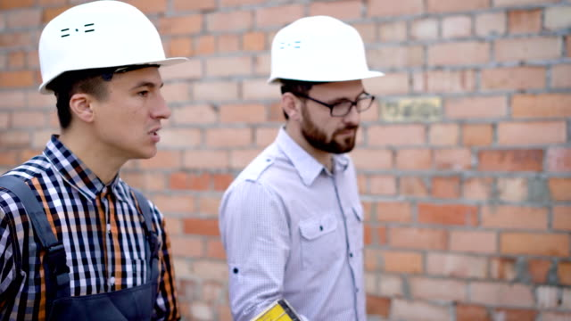 Builder walking and communicating on background of brick wall video