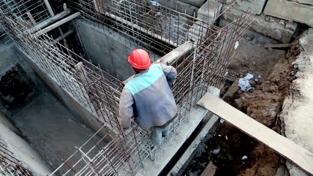 Builder with red hard hat at project site. Building of foundation video