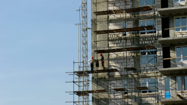 Builders erect scaffolding. Time lapse video
