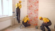 Builders hang wallpaper in the apartment. video