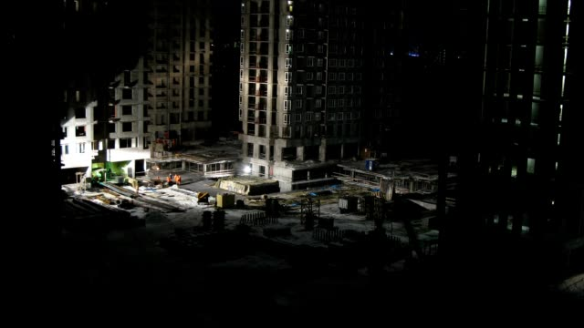 Builders work on construction site at night, time lapse video