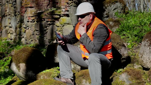 Building inspector thinking near ancient wall video