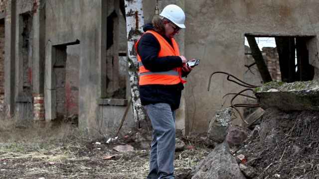 Building supervisor using tablet PC on buildings territory before demolition video
