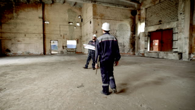 Building. The builder quickly moves to the main master of the construction site. Men shake hands and communicate to the account of errors in the construction drawing video