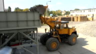 Buldozer loading broken glass into a feeder in recovery plant video