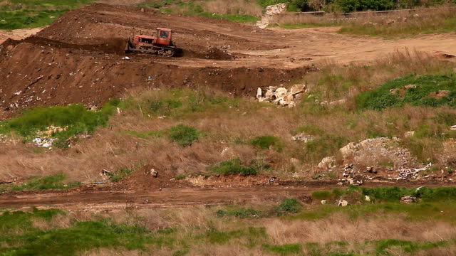 Bulldozer is leveling mound of earth video