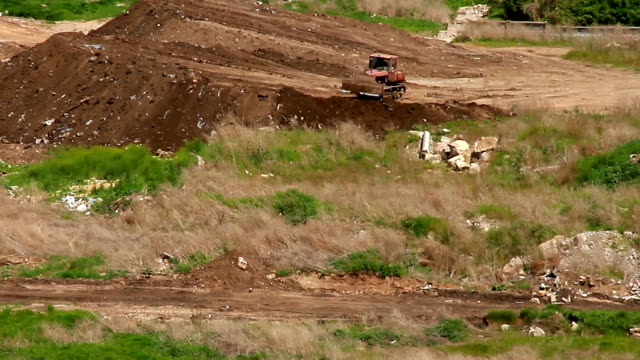 Bulldozer leveling the earth on an earthen embankment video