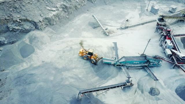 A bulldozer loads rubble in a stone quarry video