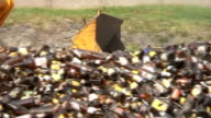 Bulldozer scooping amber bottles in glass recovery plant, close-up video