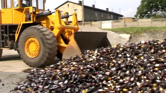 Bulldozer scooping amber bottles in glass recovery plant video