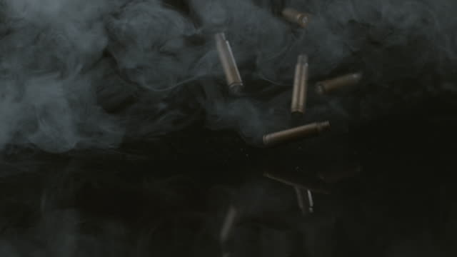 Bullet shells and smoke falling in slow motion video