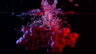 Bunch of red grapes falling into water with splashes super slow motion shot video