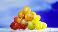 Bunch of white grapes rotating on blue sky background video