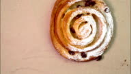 Buns with raisins rotates on a paper background top view video