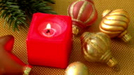 Burning candle in a Christmas setting with seasonal decorations video