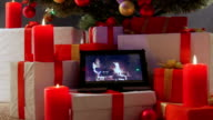 Burning candles gifts boxes and tablet computer with fireplace on screen under Christmas tree video