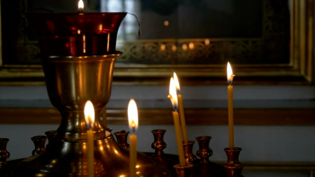 Burning candles in front of the altar in the church. Praying parishioner of the church. video