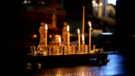 Burning candles in sconces on black blue background video
