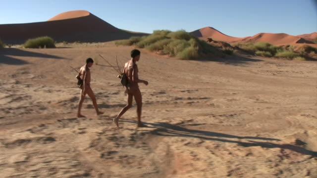 Bush people walking in Namib desert video