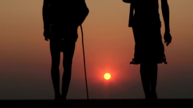Bushmen walking into the sunset on the Makgadikgadi Pans video