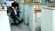 BusiBusinessman pushing co-worker through office on chair video