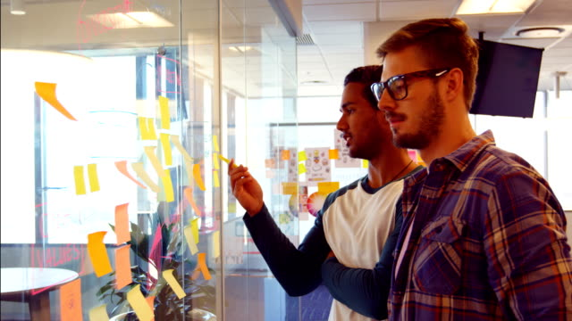 Business colleagues discussing over sticky notes video