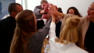 Business colleagues giving eachother high five in meeting video