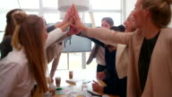 Business colleagues giving eachother high five's in meeting video