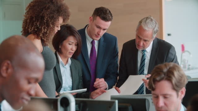 Business colleagues stand talking in a busy office, close up video